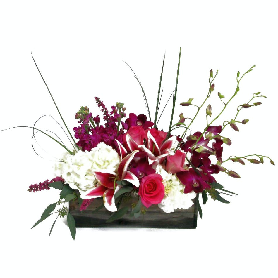 A lovely wooden container arrives filled with hydrangea, orchids, lilies, roses, stock and seeded eucalyptus.