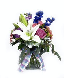 Lilies, roses, hydrangea, gerbera daisies, delphinium, stock and seeded eucalyptus arrive in this compact vase accented with a pretty ribbon.
