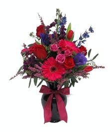 A lavish mix of roses, gerbera daisies, stock, delphinium, miniature roses, and Heather arrive in a lovely keepsake dark purple vase.
