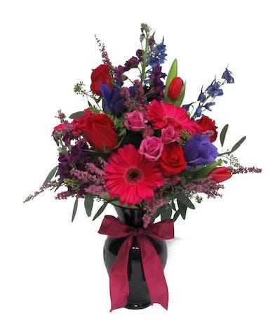 A lavish mix of roses, gerbera daisies, stock, delphinium, miniature roses, and Heather arrive in a lovely keepsake dark purple vase.