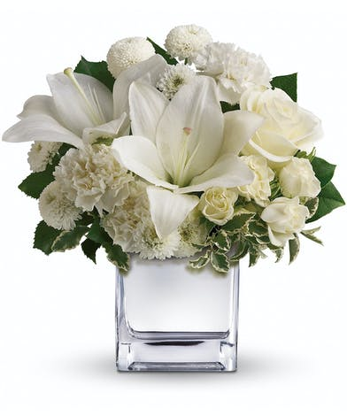 White roses, lilies and other favorites are displayed in a clear cube.